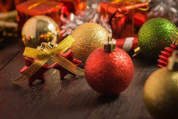selective focus Christmas background with a red ornament, golden gift box, berries on black wood blackground still life
