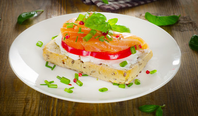Sandwich with cereals bread and salmon on a old wooden backgroun