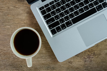 laptop and coffee cup on old wooden table