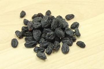 a handful of black raisins on wooden texture