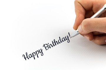"Hand writing ""Happy Birthday""  on white sheet of paper."