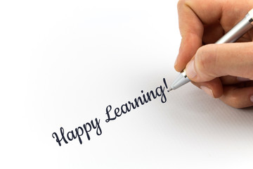 "Hand writing ""Happy Learning!"" on white sheet of paper."
