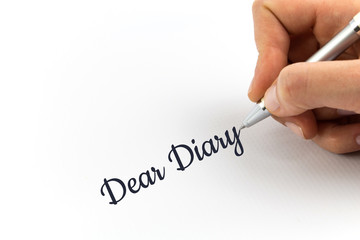 "Hand writing ""Dear Diary"" on white sheet of paper."