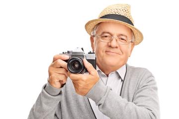 Cheerful senior gentleman holding a camera