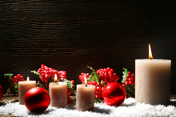 Burning candles and Christmas accessories with snow on wooden background
