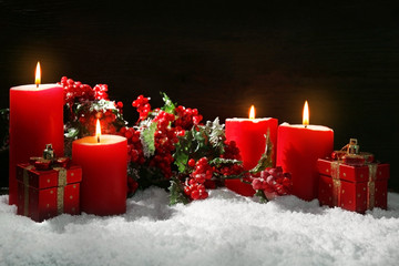 Burning candles, rowan and gift box with snow on wooden background