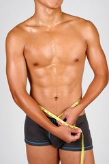 a semi-nude hunky asian male with a measuring tape around his waist