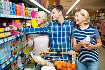 Ordinary happy family choosing dairy products