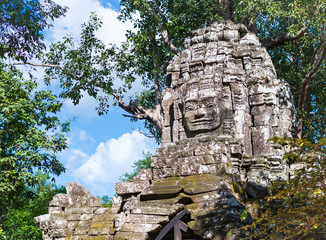 Smiling face sculpture on the stone tower in khmer Angkor Wat temple in Cambodia