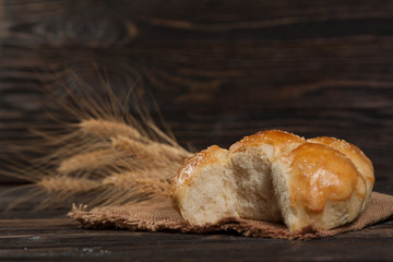 freshly baked bread with sesame seeds, wheat ears, vintage wooden background