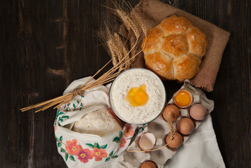 ingredients for homemade bread on vintage wooden background and towel with embroidered ears of wheat, milk, eggs, flour, dough, bread