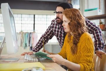 Woman writing and man looking at computer