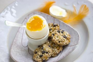 Weichgekochtes Frühstücksei mit Vollwertkeksen auf einem Teller mit einer orangefarbenen Feder
