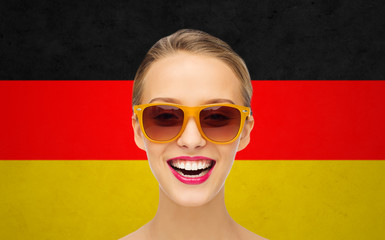 happy young woman in sunglasses over german flag