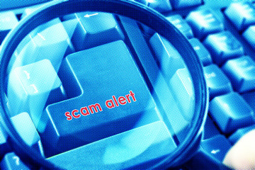 Magnifying glass on keyboard with Scam Alert word on button. Color halftone effect applied.