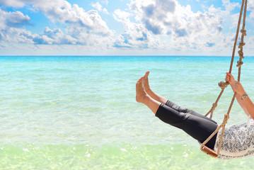 Woman swinging at tropical beach