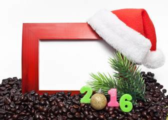 Wooden frame with red new year's cap figures and the 2016 is in coffee beans on white background