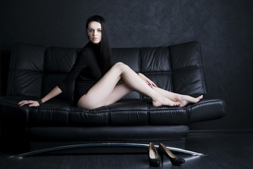 Beautiful young woman in bodysuit with long legs and long black hair sitting on a black sofa