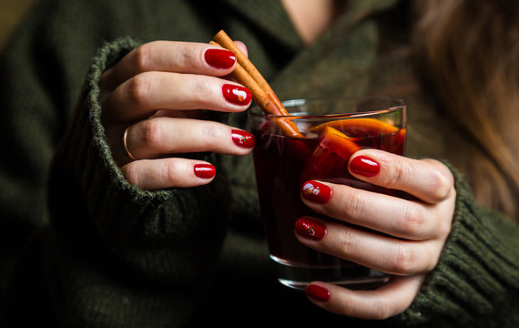 Cup with mulled wine in the hands of a girl