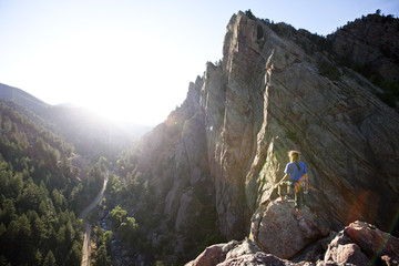 A young adult stands triumphantly on top of a 500 ft multi pitch trad climbing route in Eldorado Canyon, Colorado.