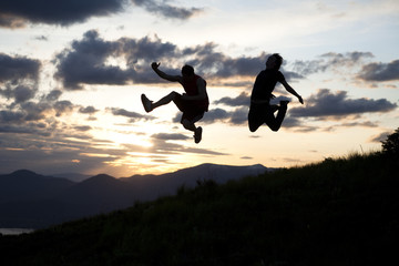 Two men jumping at sunset in Sanpoint, Idaho.
