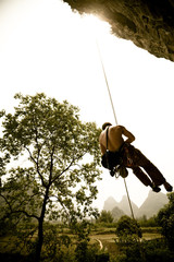 Unidentified caucasian male climber rappeling (abseiling) from Twin Gates in Yangshuo, China.  Rice paddies, scattered foliage and limestone karst mountains in the background.  Shot mid afternoon in the Spring of 2009.