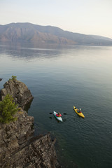 Retired couple kayak on a beautiful summer evening on Lake Pend Oreille in Sandpoint, Idaho.