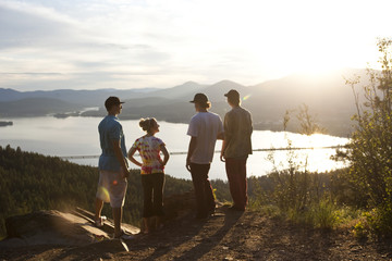 Four young adult friends talk and take in the view after hiking at sunset.