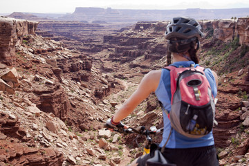 A woman on a mountain bike rides the White Rim trail and the desert landscap of Utah's Canyonland National Park.