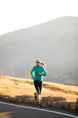 Runner, Jennifer Lee, runs along Trail Ridge Road (12,183 feet) near its apex at sunrise, Rocky Mountain National Park, Colorado.