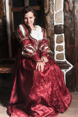 Pretty woman in red dress in retro baroque style