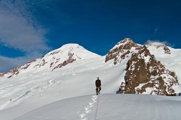 A roped climber walks towards Mount Baker and Colfax Peak in Washington, USA.