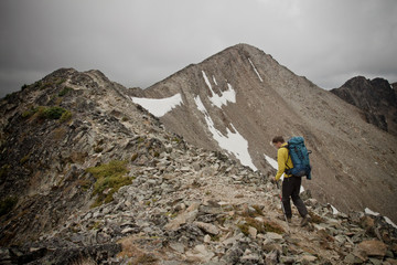 A backpacker hikes over a rocky ridgeline towards Frosty Peak in Manning Provincial Park, British Columbia, Canada.