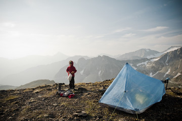 A young boy looks for food in a bag while camping on an alpine ridge high in the mountains.
