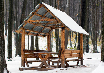 wooden arbour covered with white snow in the forest