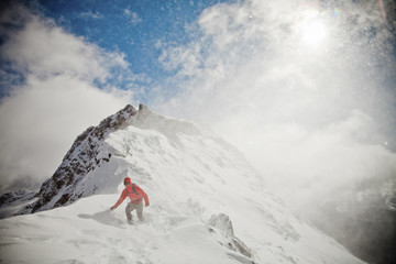 A mountaineer battles the elements on a mountain ridge near Chilliwack, BC, Canada in the North Cascade Mountain Range.