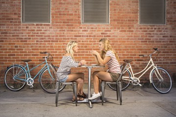 Wide angle of two women in their twenties taking a break from their bike ride to have coffee together.