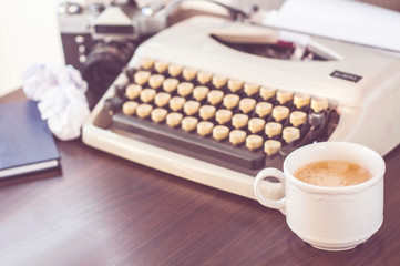 an old typewriter on old wooden table with coffee and old camera