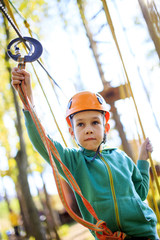 boy overcomes the obstacle course in rope park. Boy biting her lip on a complex rope climbing structure
