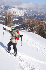 A male skier wearing a backpack and chest mounted point of view camera celebrates after skiing a deep powder run at Big Sky Resort in Big Sky, Montana.