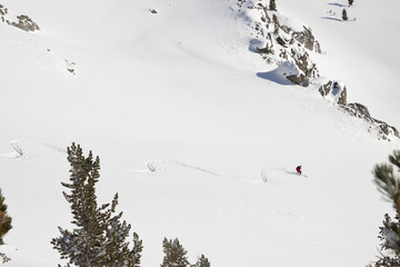 A female backcountry skier makes her way down a slope in the Beehive Basin near Big Sky, Montana.