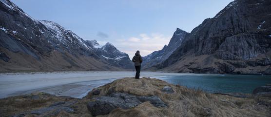 Female hiker takes in view of scenic mountain landscape at Horseid beach, Moskenesøy, Lofoten Islands, Norway