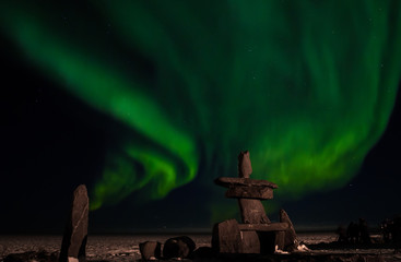 the aurora borealis, behind an inuit structure, with photographers enjoying the northern lights.