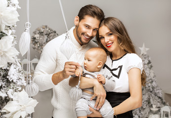 Beautiful happy familly hugging cute child in Christmas scenery