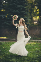 Portrait of a wedding bride posing in a white hipster style dress with flowers in her hands in the forest on sunset