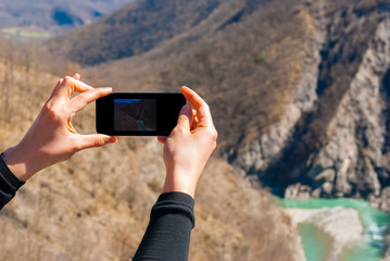 Person taking a picture of the river Trebbia with a smartphone
