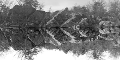 Rocks near the water in Great Falls Park, Maryland, USA. Geometry of rock formations highlighted by inverted picture of reflections.