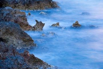 Rocky shore. Black rocks in the blue water.