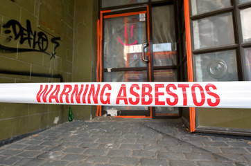 Sign reads: Warning - Asbestos removal in progress