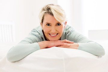 mid aged woman lying on bed at home